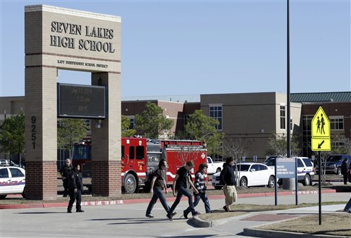 In this Jan. 13, 2014 file photo, students pass by Seven Lakes High School after being evacuated and released from school for the day after a bomb squad was called to the school after a potentially explosive device was found. Threats against schools don't just come written on bathroom walls these days. Spread using smart phone apps, social media and Internet phone services, anonymous reports of bombs or other threats of violence are forcing school evacuations and a response by police swat teams or other authorities to what in the vast majority of cases turns out to be a hoax. (AP Photo/Pat Sullivan, File)