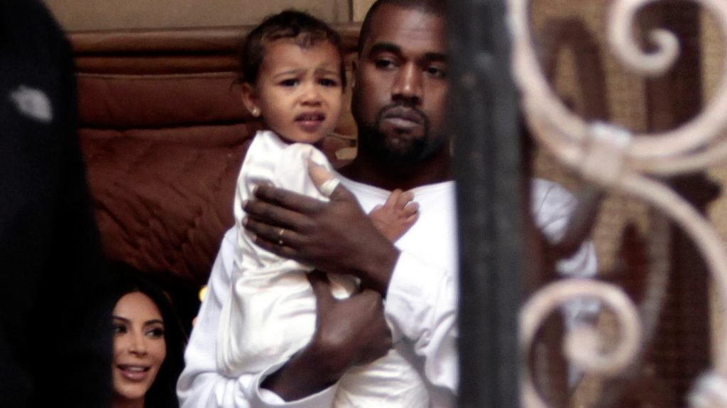 Kanye West carries North while Kim Kardashian follows, exiting the Cathedral of St. James in Jerusalem (AP Photo)