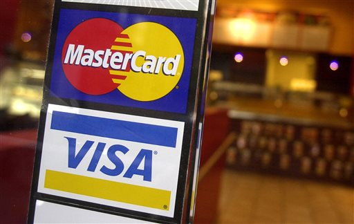 This April 22, 2005 file photo shows logos for MasterCard and Visa credit cards at the entrance of a New York coffee shop. Fair Isaac, the company behind the widely-used FICO credit score, on Thursday, April 2, 2015 announced a pilot program to help millions of Americans get easier access to credit, based on their record of paying utility bills, instead of their history of loan repayments. (AP Photo/Mark Lennihan, File)