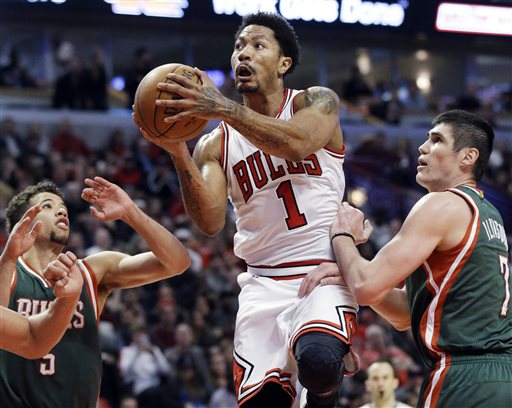 Chicago Bulls guard Derrick Rose, center, drives to the basket against Milwaukee Bucks forward Ersan Ilyasova, right, and guard Michael Carter-Williams during the second half in Game 1 of the NBA basketball playoffs Saturday, April 18, 2015, in Chicago. (AP Photo/Nam Y. Huh)