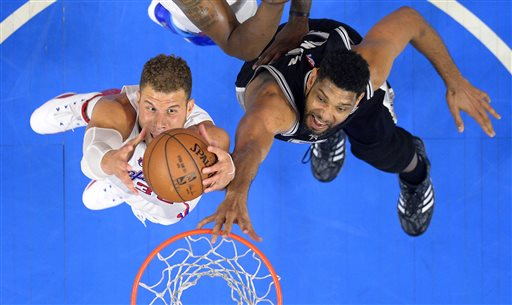 Los Angeles Clippers forward Blake Griffin, left, grabs a rebound away from San Antonio Spurs forward Tim Duncan during the first half of Game 5 of a first-round NBA basketball playoff series, Tuesday, April 28, 2015, in Los Angeles. (AP Photo/Mark J. Terrill)