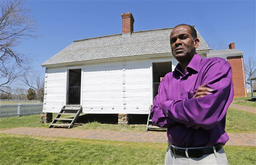 Rev. Alfred L. Jones III poses in front of the reconstructed slave quarters behind the McLean House on the grounds of Appomattox Court House National Historical Park in Appomattox, Va., Wednesday, April 1, 2015. Jones will deliver the eulogy for former slave Hanna Reynolds whose death will be remembered during the 150th anniversary of the Civil War's end. (AP Photo/Steve Helber)