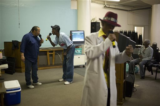 """In this Wednesday, Feb. 18, 2015 photo, Pastor Tony Stallworth, left, and Ronnie """"Sidewalk Slim"""" Shepherd sing along with Robert Verdine, foreground, during karaoke night the Central City Community Church of the Nazarene on Skid Row in Los Angeles. As people harmonize on Beatles songs, they begin to lock out the ugliness outside, where a misdirected look can launch a knife fight in a second. Where across 50 square blocks on the edge of City Hall and other landmarks that represent the rich and powerful the streets reek with the smell of urine. Where some 1,700 people bed down on filthy sidewalks every night. (AP Photo/Jae C. Hong)"""