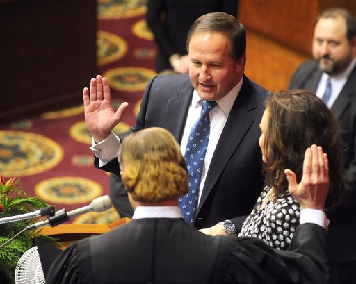 "In this Jan. 7, 2015, file photo, John J. Diehl Jr., center, is sworn in as the Speaker Pro Tem of the House of Representatives during the opening of the Missouri legislature in Jefferson City, Mo. Diehl apologized Wednesday, May 13, 2015, for his ""poor judgment"" following a newspaper report that he had exchanged sexually charged text messages with a college student who was serving as a Capitol intern. (Don Shrubshell/The Columbia Daily Tribune via AP, File)"