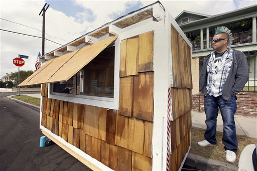 "Los Angeles resident Elvis Summers poses with his tiny house on wheels he built for a woman who had been sleeping on the streets in his South Los Angeles neighborhood on Thursday, May 7, 2015. Summers never thought more than 5.6 million people would watch a YouTube video of him constructing the 8-foot-long house for Irene ""Smokie"" McGhee, 60, a grandmother who's been homeless for more than a decade. He estimates he spent less than $500 on plywood, shingles, a window and a door. (AP Photo/Damian Dovarganes)"