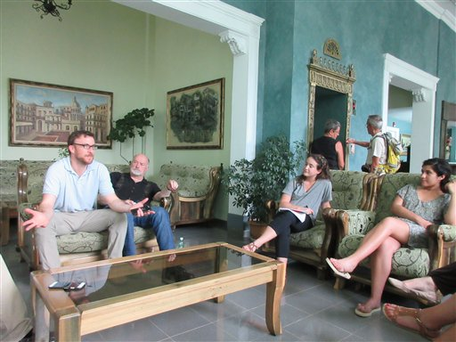 In this May 15, 2015 photo, Washington State University, WSU, professors Benjamin Shors and Ed Rabel, talk with students including Jessica Shapiro, second from right, and Selena Alvarado, at the Park View Hotel in Havana. They were part of a group of journalism students from WSU visiting Cuba on an educational trip to meet with Cuban media and Havana residents. The group is among an increasing number of Americans to visit Havana since President Barack Obama announced a thaw in U.S.-Cuba relations. (AP Photo/Beth J. Harpaz)