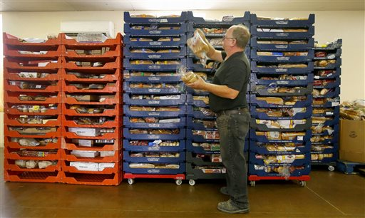 Randy Finley, the operations manager at The Church on Fillmore, looks through some of the bread at the food pantry at the church Monday, May 18, 2015, in Phoenix. Hundreds of families line up on Tuesdays to get food and clothing from the thrift shop at the church. (AP Photo/Ross D. Franklin)