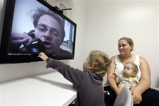 In this photo taken on Tuesday, May 5, 2015, inmate Jesse Cole is shown on a television screen as his son William, 4, center, reaches to touch the screen while his mother, Edna, holds 8-month-old Jesse James, during a video visitation with at the Fort Bend County Jail, in Richmond, Texas. Prisoners' rights advocates are worried that the growing use in the U.S. of video technology to facilitate visits between inmates and their family and friends at county jails and prisons is part of a trend to eliminate the more traditional in-person visit. But officials who run these facilities say video visitation has been a boon to their efforts to improve security and increase visiting hours. (AP Photo/David J. Phillip)
