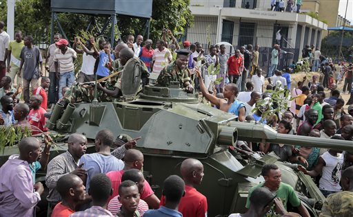 Demonstrators celebrate what they perceive to be an attempted military coup d'etat, with army soldiers riding in an armored vehicle in the capital Bujumbura, Burundi Wednesday, May 13, 2015. Police vanished from the streets of Burundi's capital Wednesday as thousands of people celebrated a coup attempt against President Pierre Nkurunziza. (AP Photo/Berthier Mugiraneza)