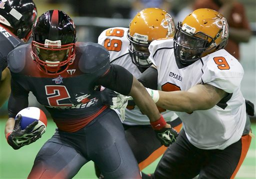 In this photo from May 16, 2015, Omaha Beef players Jesse Robertson (9) and Demichael McWilliams (99) tackle Sioux City Bandits' Fredrick Bruno (2) in a Champions Indoor Football league game in Sioux City, Iowa. Robertson doesn't mind living a Spartan existence in Omaha if that's what it takes to move to a higher level someday. The Omaha Beef provides lodging at the Best Western for him and about a half-dozen other players who have no local ties. The team also gives the out-of-towners vouchers for meals at restaurants that are sponsors. The entire team meets on Fridays for a pregame meal of chicken wings at a Hooter's. (AP Photo/Nati Harnik)