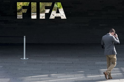 """A man walks next to the FIFA logo at the FIFA headquarters in Zurich, Switzerland, Wednesday morning, May 27, 2015. Swiss federal prosecutors say they have opened criminal proceedings related to the awarding of the 2018 and 2022 World Cups. The prosecutors' office says the proceedings are against """"persons unknown on suspicion of criminal mismanagement and of money laundering"""" in connection with the votes won by Russia and Qatar. (Ennio Leanza/Keystone via AP)"""
