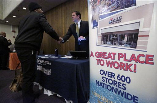 In this April 22, 2015 photo, a sign at a recruiting station for Leslie's Pool supplies boasts that it is a great place to work during a National Career Fairs job fair, in Chicago. The Labor Department releases employment data for April on Friday, May 8, 2015. (AP Photo/M. Spencer Green)
