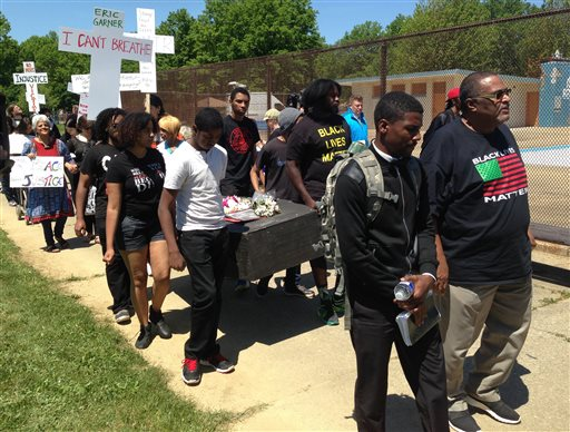 Protestors walk in a mock funeral procession in a park after the verdict of officer Michael Brelo, on Saturday, May 23, 2015, in Cleveland. Brelo, a police officer charged in the shooting deaths of two unarmed suspects, Timothy Russell and Malissa Williams, was acquitted, Saturday. (AP Photo/Andrew Welsh-Huggins)