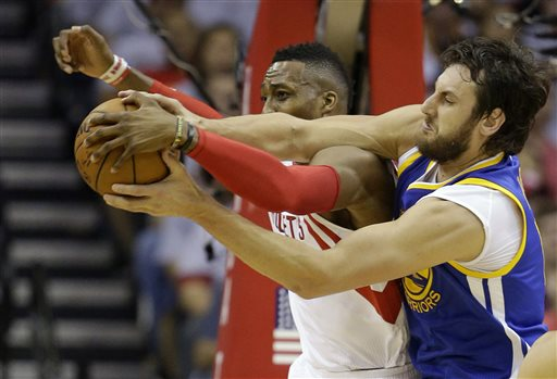 Houston Rockets center Dwight Howard, left, and Golden State Warriors center Andrew Bogut, right, go after a rebound during the first half in Game 3 of the NBA basketball Western Conference finals Saturday, May 23, 2015, in Houston. (AP Photo/David J. Phillip)