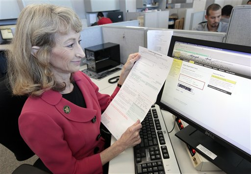 FILE - In this Sept. 19, 2012 file photo, then-California Secretary of State Debra Bowen, shows a online voter registration system as she holds a traditional written form in Sacramento, Calif. Applicants can fill out a form online that will be checked  against their driver's license or the state identification card held by the California Department of Motor Vehicles. When President Barack Obama was first elected in 2008, only two states offered an online website where citizens could register to vote. Five states now allow citizens without a state identification or driver's license to register to vote online: California, Delaware, Minnesota, Missouri, and Virginia.  (AP Photo/Rich Pedroncelli, File)