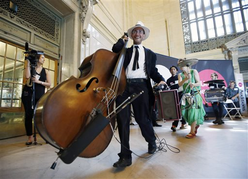 Seth Myers of Receta Secreta, carries his bass away from the stage after auditioning for judges in Grand Central Terminal's Vanderbilt Hall in New York, Tuesday, May 19, 2015. About 70 musicians and others showed up Tuesday at the station to vie for official permission to set up their acts on an underground platform or walkway. (AP Photo/Kathy Willens)