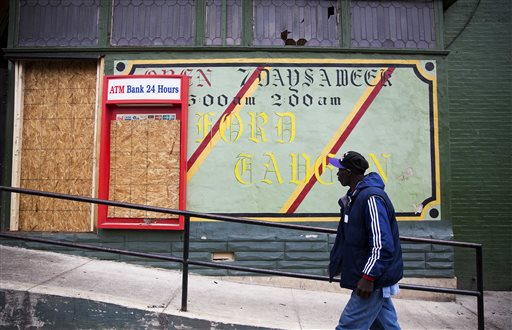 A man walks past the damaged Oxford Tavern on Thursday, April 30, 2015, in Baltimore. Richard Sung Kang's liquor store and bar was hit by looters Monday, during a riot over the police-involved death of neighborhood resident Freddie Gray. The business wasn't torched like the nearby CVS pharmacy, but its doors and windows were broken and cash and inventory stolen, leaving shelves bare. Now the 49-year-old South Korean immigrant must decide whether to reopen. If so, it could mean taking on more debt and paying higher insurance premiums. (AP Photo/David Goldman)