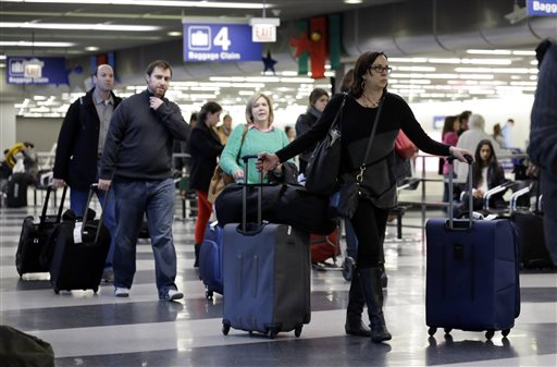 In this Dec. 1, 2013 file photo, travelers walk through terminal 3 baggage claim at O'Hare International airport in Chicago. The Department of Transportation on Monday, May 4, 2015 said that airline net income fell to $7.5 billion in 2014 from $12.2 billion in 2013. Airlines collected $3.5 billion in bag fees, a 5 percent increase over 2013. (AP Photo/Nam Y. Huh, File)
