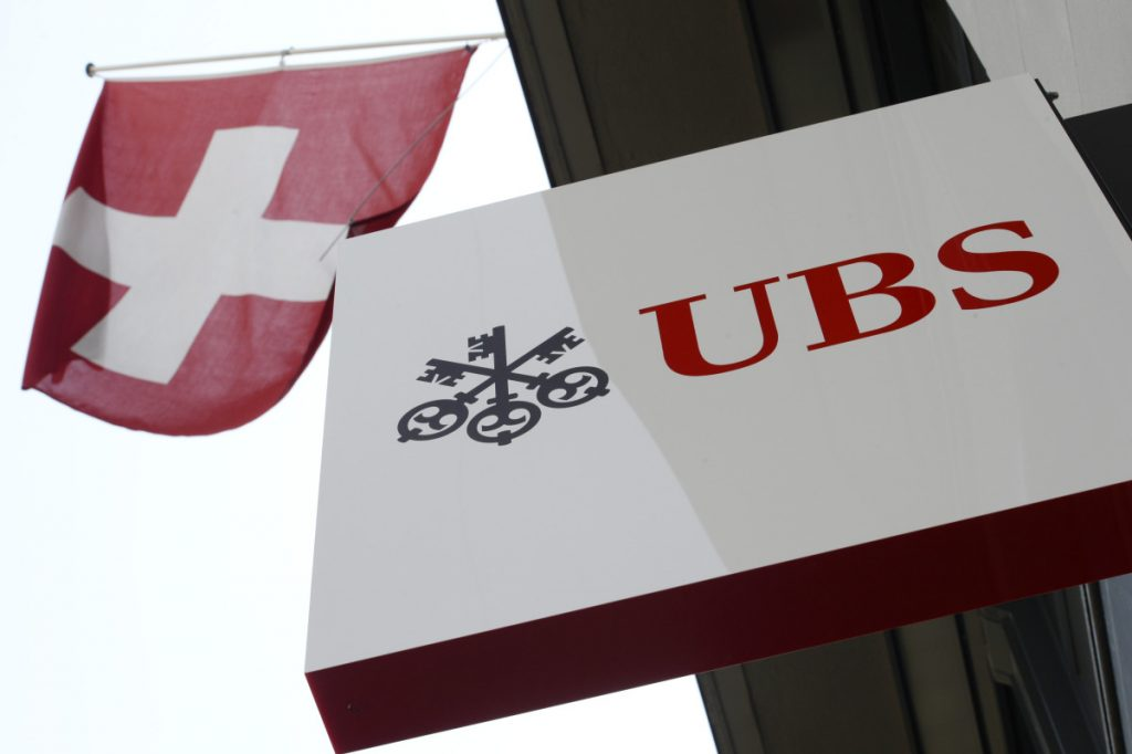 The April 24, 2014 file photo shows the logo of Swiss bank UBS and the Swiss flag in Zurich, Switzerland. (Steffen Schmidt/AP Photo)