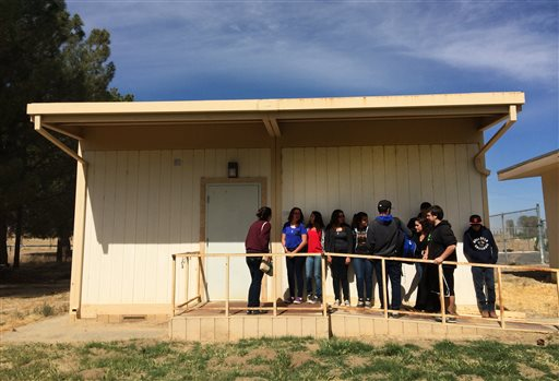 In this April 30, 2015 photo, students line up to take part in new Common Core-aligned standardized tests at the Cuyama Valley High School in New Cuyama, Calif. The Cuyama Joint Unified School District is 60 miles from the nearest city and has Internet connections about one-tenth the minimum speed recommended for the modern U.S. classroom. Across the country, school districts in rural areas and other pockets with low bandwidth are confronting a difficult task of administering new Common Core-aligned standardized tests to students online. (AP Photo/Christine Armario)