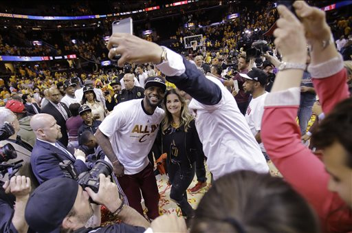Cleveland Cavaliers forward LeBron James poses for a selfie with fans after the Cavaliers defeated the Atlanta Hawks 118-88 in Game 4 of the NBA basketball Eastern Conference finals for a sweep, Tuesday, May 26, 2015, in Cleveland. (AP Photo/Tony Dejak)