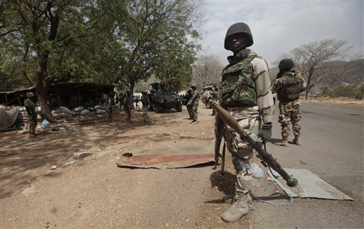 In this file photo taken Wednesday, April 8, 2015, Nigerian Soldiers man a check point in Gwoza, Nigeria, a town newly liberated from Boko Haram. Nigeria's military says it is moving 200 girls and 93 women from a northeastern forest where they were rescued from Boko Haram extremists. (AP Photo/Lekan Oyekanmi,File)