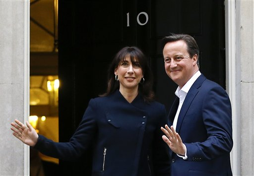 Britain's Prime Minister David Cameron and his wife Samantha return to 10 Downing Street in London, Friday, May 8, 2015.  The Conservative Party surged to a surprisingly commanding lead in Britain's parliamentary election, with returns Friday backing an exit poll's prediction that Prime Minister David Cameron would remain in 10 Downing Street. (AP Photo/Kirsty Wigglesworth)