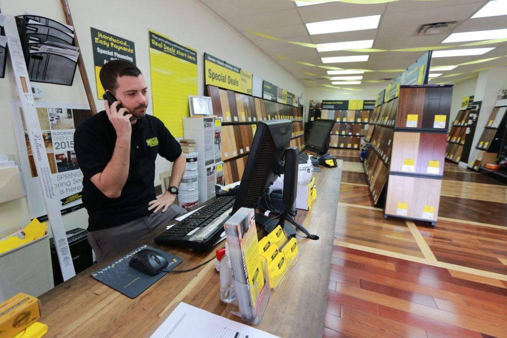 "Kiel Skrobacz, an assistant store manager at Lumber Liquidators in Lutz, Fla., speaks on the phone on Thursday, March 12, 2015. A ""60 Minutes"" expose reported the company's Chinese-made laminate flooring contained high levels of formaldehyde, a carcinogen. The founder and chairman of the company said Friday that the retailer currently has no plans to stop selling laminate flooring made in China, even as it continues to face fallout from the report that questioned the safety of such laminates. (AP Photo/Tampa Bay Times, Rachel Crosby)"