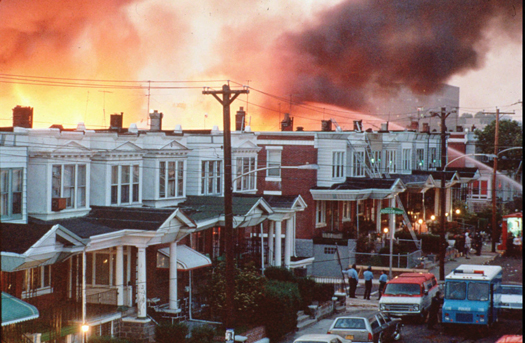 Row houses in Philadelphia burn after officials dropped a bomb on the MOVE house in this May 1985 photo from files. Ramona Africa, the lone adult survivor of the May 13, 1985 fire, and two other MOVE members sued the city of Philadelphia, and the former police and fire commissioners for financial damages in what was the first trial in court to address the MOVE bombing. (AP Photo)