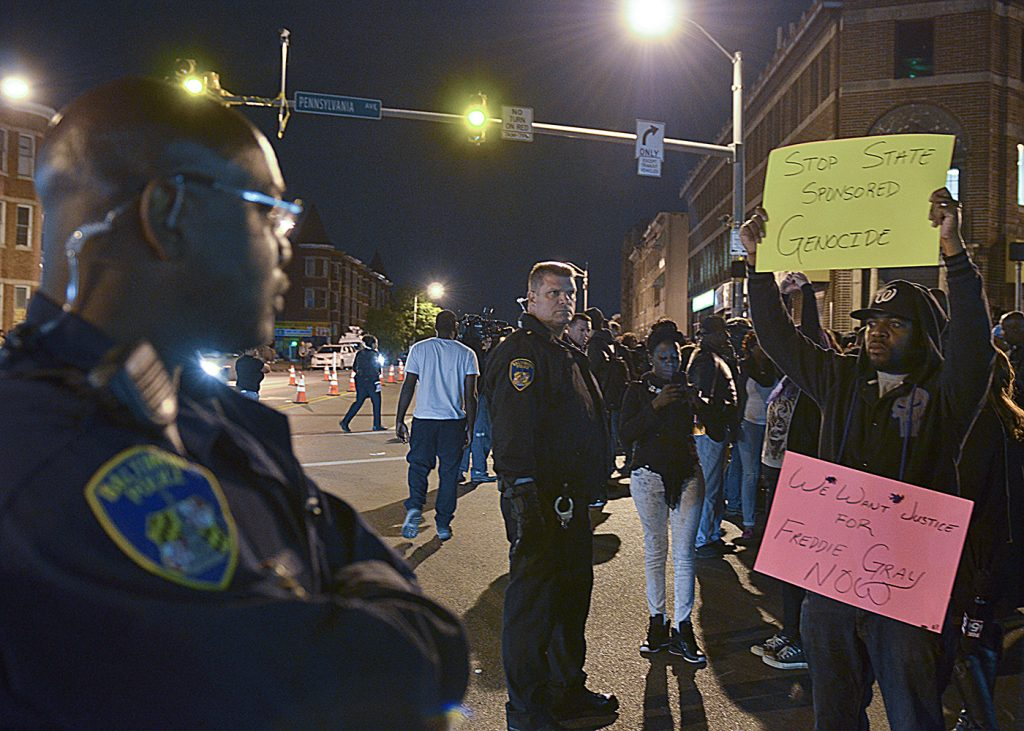 Protesters call for justice for Freddie Gray as Baltimore police officers watch. (Freddie Allen/NNPA News Wire Service)