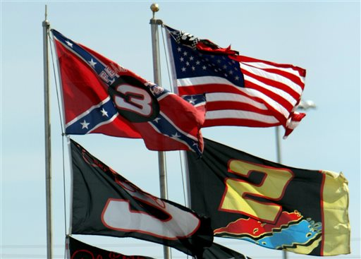 In this Feb. 15, 2008, file photo, flags, including a Confederate flag, fap in the wind during practice for the NASCAR Sprint Cup Series Daytona 500 auto race at Daytona International Speedway in Daytona Beach, Fla.  NASCAR is backing South Carolina Gov. Nikki Haley's call to remove the Confederate flag from the South Carolina Statehouse grounds in the wake of a massacre at a Charleston church, it said in a statement Tuesday, June 23, 2015. Though NASCAR bars the use of the flag in any official capacity, many fans fly the flag at their races. (AP Photo/Darryl Graham, File)