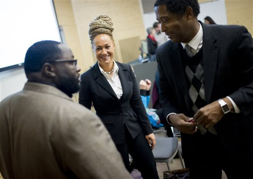 In this Friday, Jan. 16, 2015, file photo, Rachel Dolezal, center, Spokane's newly-elected NAACP president, smiles as she meets with Joseph M. King, of King's Consulting, left, and Scott Finnie, director and senior professor of  Eastern Washington University's Africana Education Program, before the start of a Black Lives Matter Teach-In on Public Safety and Criminal Justice, at EWU, in Cheney, Wash. Dolezal's family members say she has falsely portrayed herself as black for years. (Tyler Tjomsland/The Spokesman-Review via AP, File)