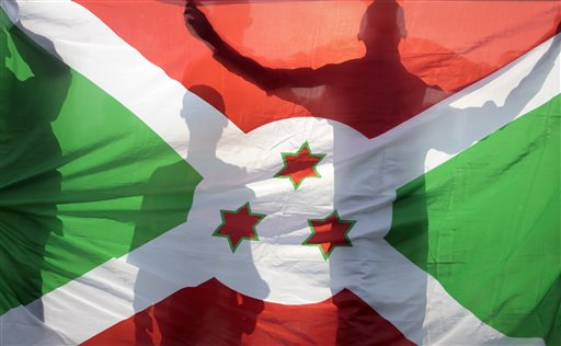 Mourners are silhouetted behind the Burundi national flag as they march in memory of Theogene Niyondiko, who was shot dead by police during an opposition demonstration last Friday in the Musaga neighborhood, in the capital Bujumbura, Burundi, Tuesday, June 9, 2015. Civic groups in Burundi on Tuesday rejected a U.N. facilitator of talks between the government and those opposed to a third term for President Pierre Nkurunziza. (AP Photo/Gildas Ngingo)