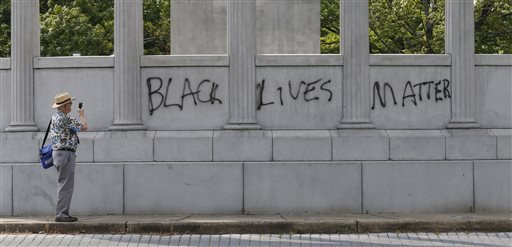 """A passerby photographs the spray painted message of """"Black Lives Matter"""" that was painted on a monument to former Confederate President Jefferson Davis on Monument Avenue in Richmond, Va., Thursday, June 25, 2015. The vandalism comes after a mass shooting in Charleston South Carolina has sparked a nationwide debate on the public display of Confederate imagery.  (AP Photo/Steve Helber)"""
