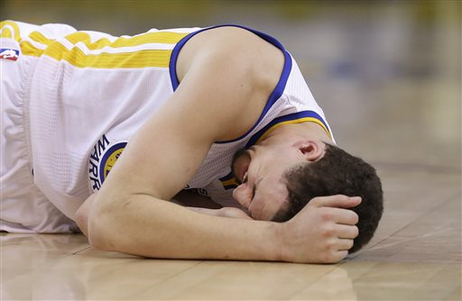 In this photo taken May 27, 2015, Golden State Warriors guard Klay Thompson reacts after taking a knee to his head from Houston Rockets forward Trevor Ariza during the second half of Game 5 of the NBA basketball Western Conference finals. The Warriors hope to get healthy and stay in tune over the next week before facing the Cleveland Cavaliers in the NBA Finals. Thompson needs to pass through the league's concussion protocol and Stepehen Curry is trying to get his aching body back at full strength. (AP Photo/Ben Margot)