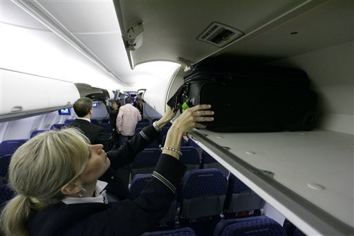 In this April 13, 2009 file photo, American Airlines flight attendant Renee Schexnaildre demonstrates the overhead baggage area during a media preview of the airline's new Boeing 737-800 jets, at Dallas Fort Worth International Airport in Grapevine, Texas. Global airlines on Tuesday, June 9, 2015 announced a new guideline that recommends shrinking carry-on bags, in an effort to free up space in packed overhead bins. (AP Photo/Donna McWilliam, File)