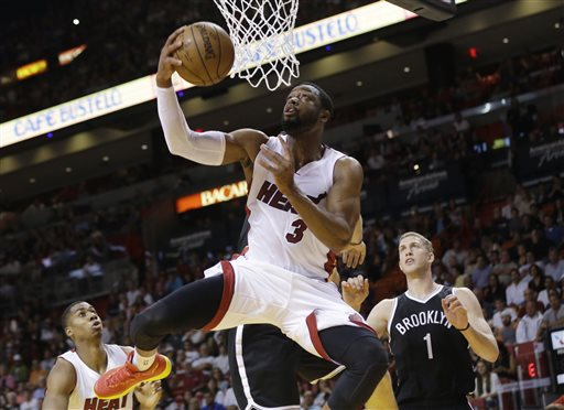 In this Jan. 4, 2015, file photo, Miami Heat guard Dwyane Wade (3) shoots in front of Brooklyn Nets center Mason Plumlee (1) during the first half of an NBA basketball game in Miami. Wade announced Monday, June 29, 2015, that he will elect to become a free agent. (AP Photo/Lynne Sladky, File)