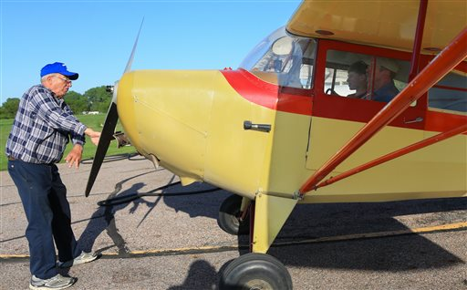 In this June 1, 2015 photo, Gene Martin, owner of Martin Field, left, manually starts the engine of an Aeronca Chief airplane as flight instructor Scott Currie, right and 12-year-old flight student Pierce Turner, right, sit in the aircraft before taking off, in South Sioux City, Neb. Martin recalls when teenagers would bike out to the airfield and pay for flight lessons with the money they earned from paper routes. Now, young people seem more interested in video games or driving cars, Martin said. The number of flight instructors at his field as fallen from 12 to 3, and they're not especially busy. (AP Photo/Nati Harnik)