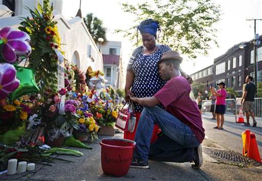 """Allen Sanders, right, kneels next to his wife Georgette, both of McClellanville, S.C., as they pray at a sidewalk memorial in memory of the shooting victims in front of Emanuel AME Church Saturday, June 20, 2015, in Charleston, S.C. """"You can't have love and hate residing in the heart at the same time,"""" said Georgette. """"We're just going to have to love one another,"""" her husband added. (AP Photo/David Goldman)"""