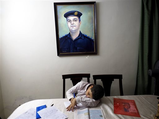 """In this picture taken on Oct. 17, 2014, 13-year-old Adham Ehab Anwar, whose policeman father was shot to death in an attack on his station after the bloody security force breakup of Islamist sit-ins in Cairo in 2013, studies geometry at his home in 6 October city, a suburb southwest of Cairo, in Giza, Egypt. Psychiatrist Eman Gaber, who leads a rehabilitation program for traumatized children, says there are not any statistics about how many children suffered trauma in Egypt's recent unrest, though it's """"still hard not to be exposed to any violence,"""" whether that was rioting in their neighborhood or images seen on television or the Internet."""" (AP Photo/Hamada Elrasam)"""