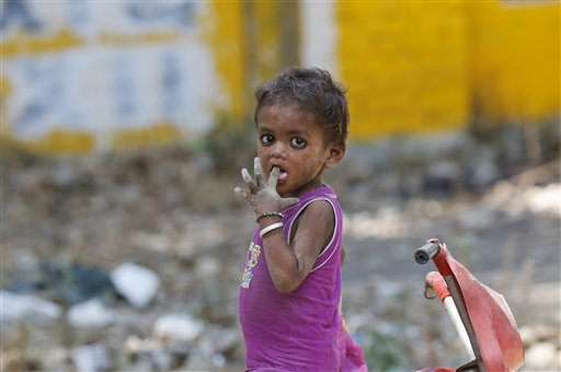 An Indian homeless child reacts to camera as he plays on a roadside in Allahabad, India, Tuesday, June 23, 2015. A new report by UNICEF warns that economic growth is still failing to help millions of the world's poorest children. In India, there are countless children living with grinding poverty, sleeping on sidewalks, begging at traffic intersections and relying on government-run lunch programs that often provide their only full meal for the day. (AP Photo/Rajesh Kumar Singh)