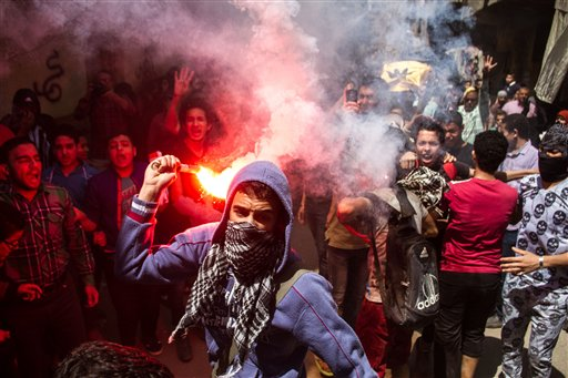 In this April 24, 2015 file photo, an Egyptian youth carries a lit flare as supporters of the Muslim Brotherhood gather in the El-Mataria neighborhood of Cairo, Egypt, to protest the 20-year sentence for ousted president Mohammed Morsi and verdicts against other prominent figures of the Brotherhood. Egyptian police are increasingly detaining activists and students in secret, snatching them from homes or the street and holding them for weeks as their families scramble to find them. Activists have tracked well over 100 such disappearances the past two months, a sign of the unchecked power of security agencies in the country. (AP Photo/Belal Darder, File)