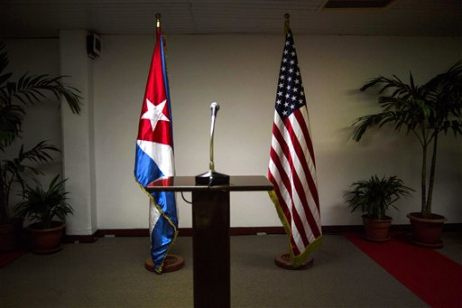 In this Jan. 22, 2015 file photo, a Cuban and U.S. flag stand before the start of a press conference on the sidelines of talks between the two nations in Havana, Cuba.  Half a year after the Dec. 17, 2014, announcement, the two countries were yet to announce what observers called an imminent deal on opening embassies in each other's capitals. (AP Photo/Ramon Espinosa, File)