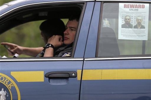 A wanted poster is displayed in the window of a state police officer's car near Dannemora, N.Y., Friday, June 12, 2015.  Squads of law enforcement officers are heading out for a seventh day, searching for David Sweat and Richard Matt, two murderers who escaped from Clinton Correctional Facility, a maximum-security prison in northern New York. (AP Photo/Seth Wenig)
