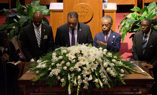 The Rev. Al Sharpton, center right, and Rev. Jesse Jackson, center, stand over the casket of Ethel Lance during her funeral service, Thursday, June 25, 2015, in North Charleston, S.C. Lance was one of the nine people killed in the shooting at Emanuel AME Church last week in Charleston. (AP Photo/David Goldman)