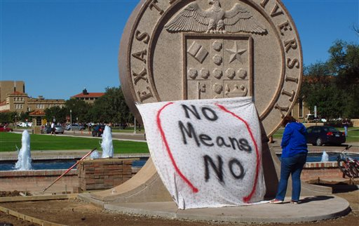 "In this Wednesday, Oct. 1, 2014 file photo, Texas Tech freshman Regan Elder helps drape a bed sheet with the message ""No Means No"" over the university's seal at the Lubbock, Texas campus to protest what students say is a ""rape culture"" on campus. A picture of a banner at a Sept. 20 Phi Delta Theta fraternity gathering, briefly posted online, read, ""No Means Yes,"" followed by a graphic sexual remark. A study by the Canadian Institutes of Health Research and the University of Windsor published on Wednesday, June 10, 2015 found that a program that taught college women ways to prevent sexual assault cut in half the chances they would be raped over the next year. It was the first large, scientific test of resistance training, and the strong results should spur more universities to offer it, experts say. (AP Photo/Betsy Blaney)"