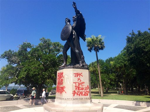 A statue memorializing the Confederacy is spray-painted several days after a shooting at a historic black church Sunday, June 21, 2015, in Charleston, S.C. Police spokesman Charles Francis said city workers used a tarp to cover up the graffiti marking the stone pedestal beneath the statue. He said he didn't know when the graffiti was spray-painted there, but said it would be cleaned off. (AP Photo/WCSC-TV, Philip Weiss)