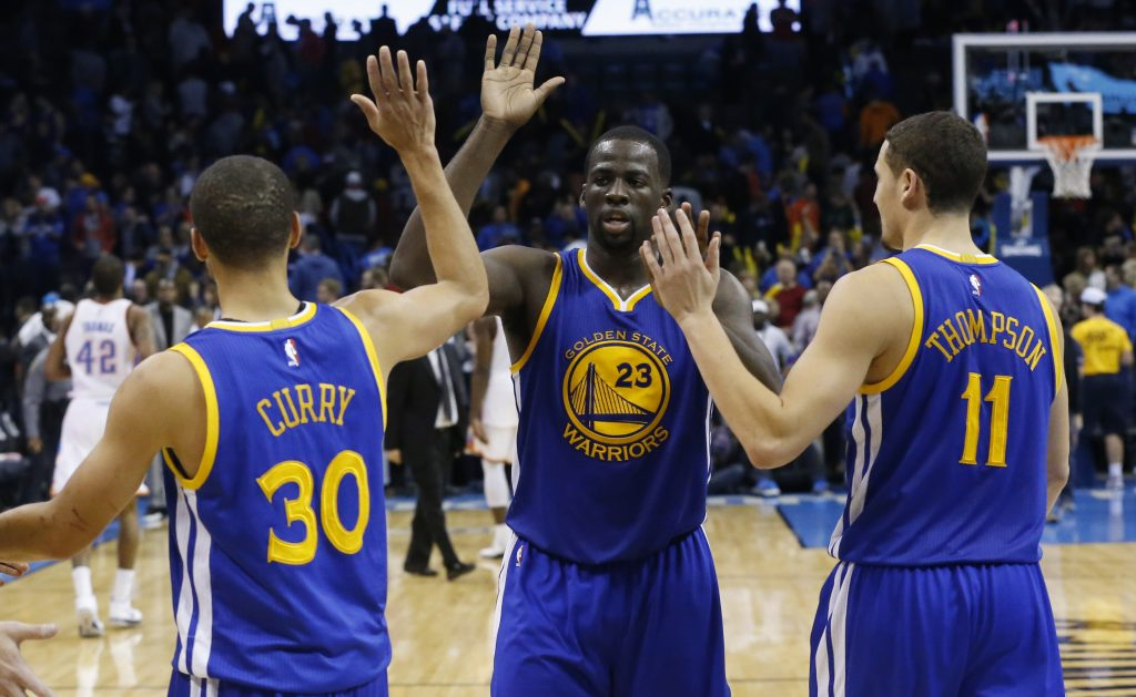 Golden State Warriors' Stephen Curry (30), Draymond Green (23) and Klay Thompson (11) celebrate after defeating the Oklahoma City Thunder in an NBA basketball game in Oklahoma City, Sunday, Nov. 23, 2014. Golden State won 91-86. (AP Photo/Sue Ogrocki)
