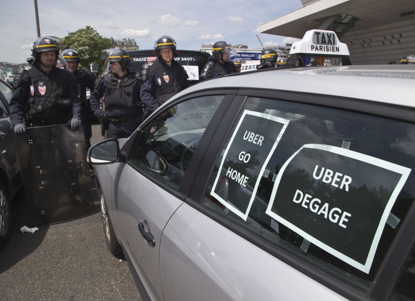 """Riot police officers stand next to a cab with posters which reads, """"Uber go home"""" and """"Uber get out out,"""" during a taxi drivers demonstration in Paris, France, Thursday, June 25, 2015. (Michel Euler/AP)"""