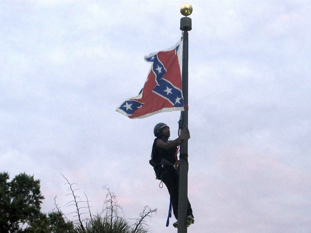 Bree Newsome of Charlotte, N.C., climbs a flagpole to remove the Confederate battle flag at a Confederate monument in front of the Statehouse in Columbia, S.C., on Saturday, June, 27, 2015. (AP Photo/Bruce Smith)